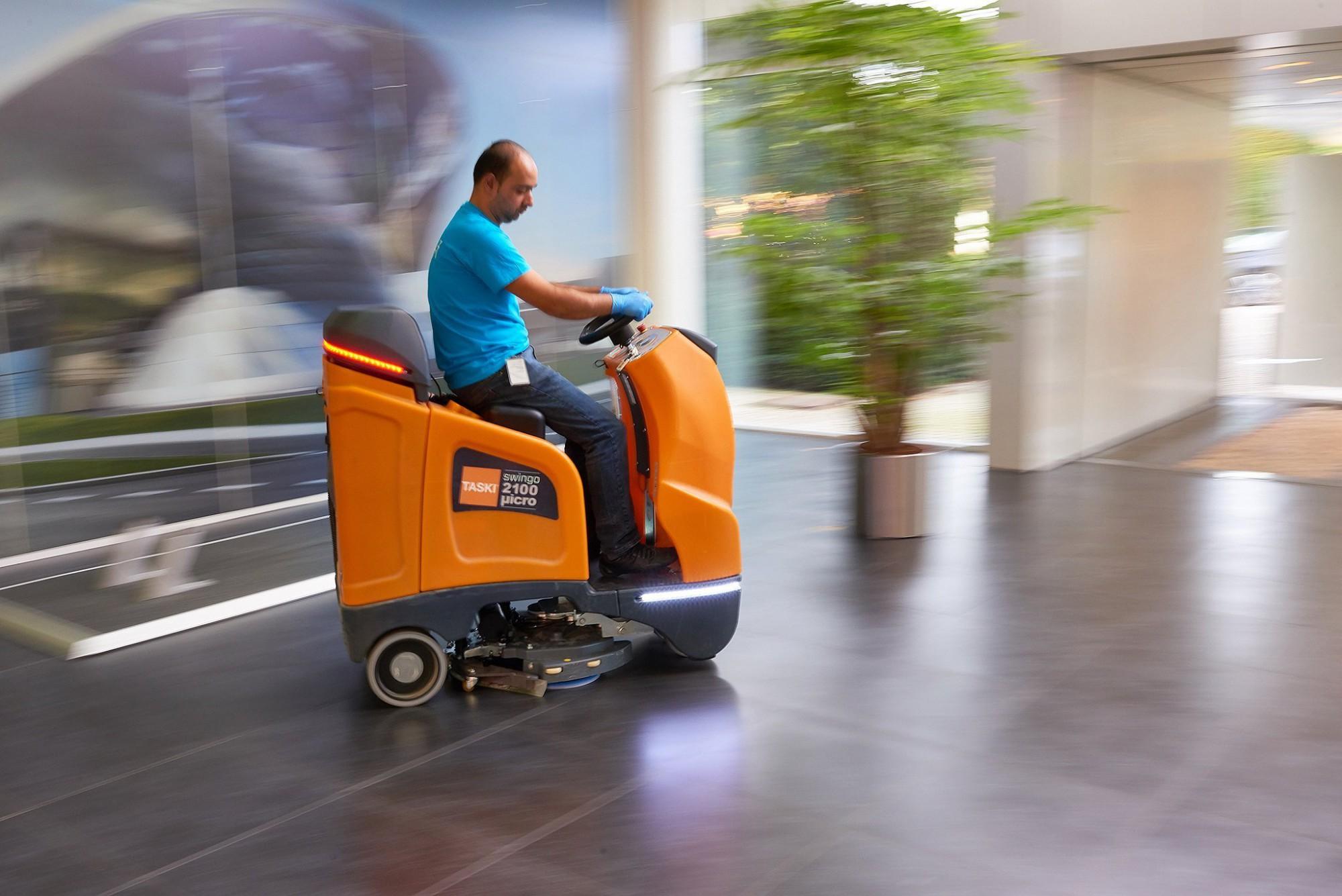 Afbeelding: Bedrijfsfotografie voor Group-F, poetsen van een kantoorgebouw met een kuismachine.