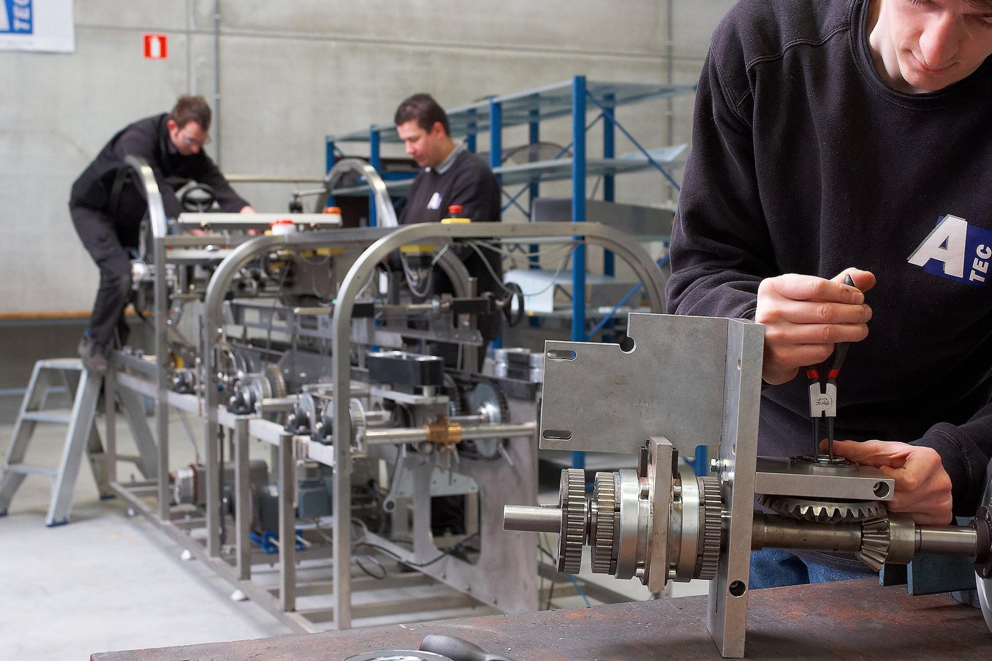 Afbeelding: Bedrijfsreportage fotografie van A tec, montage van een inpakmachine in atelier.